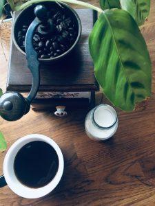 Vintage coffee grinder with black coffee, plant and milk